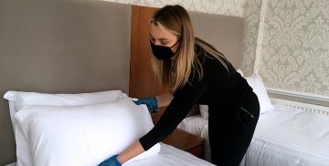 Woman fixes pillow cases on hotel bed wearing gloves and face mask